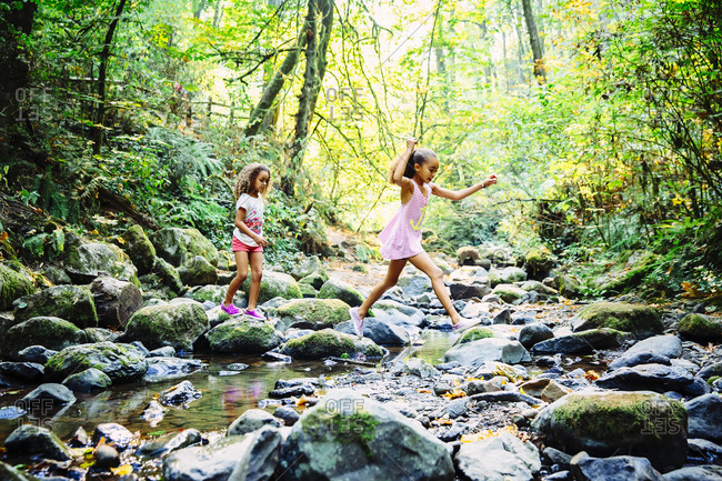 Mixed race sisters exploring stream