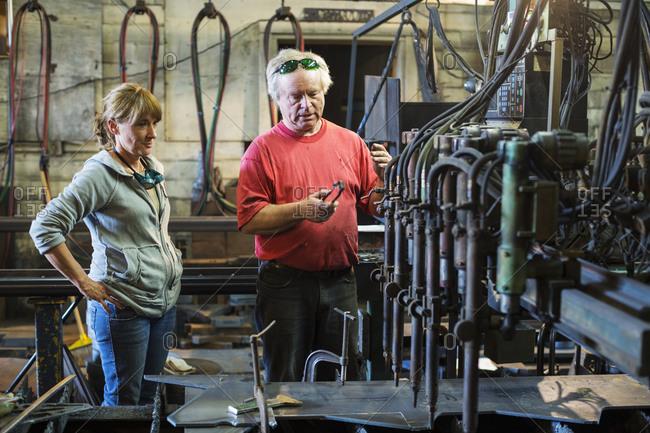 Caucasian workers talking in factory