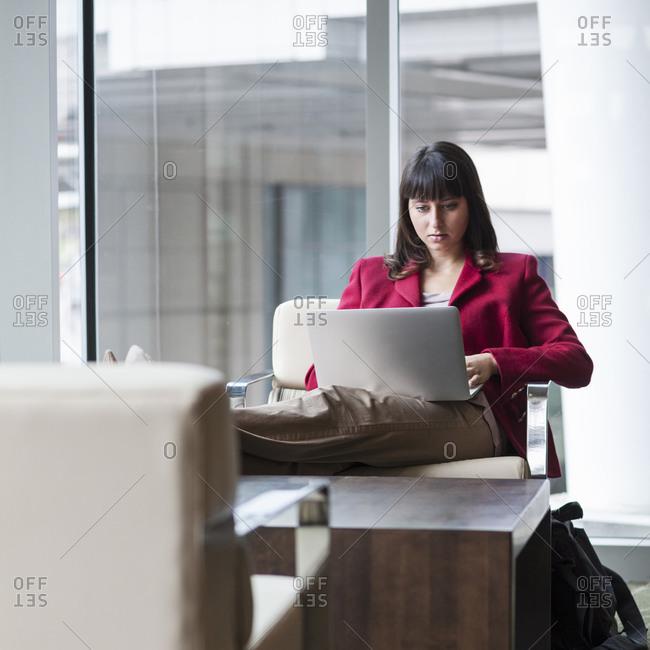 Hispanic businesswoman using laptop in office lounge