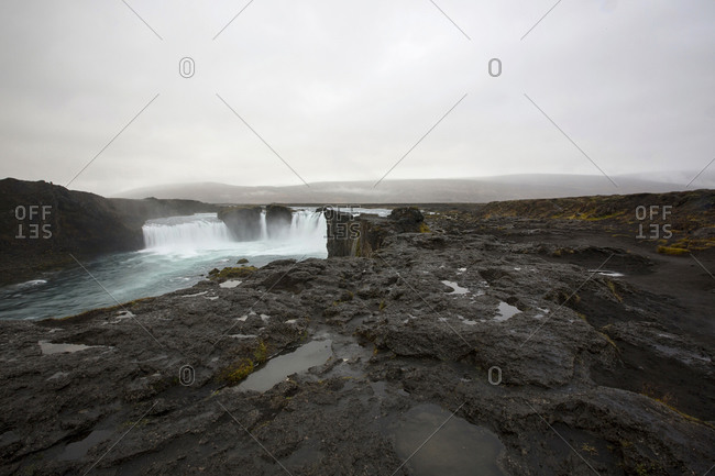 Rock formation cliffs near remote waterfall