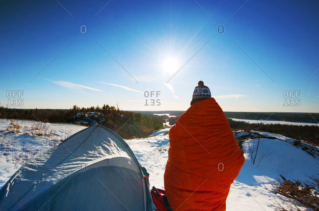 Hiker standing at snowy campsite