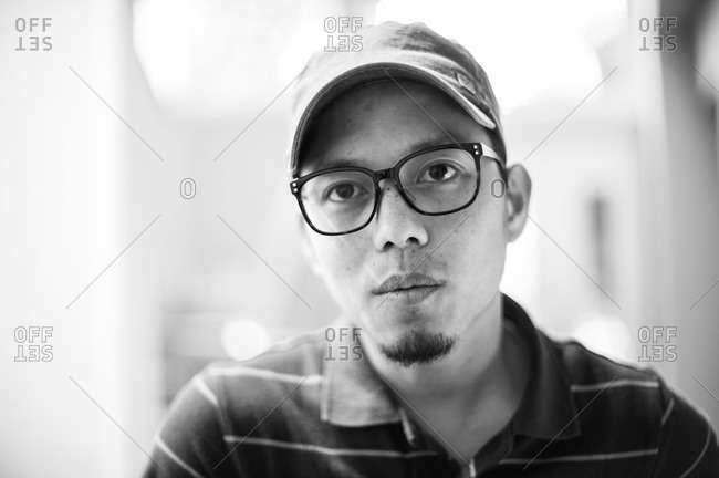 Portrait of an Asian man with glasses, cap and a goatee