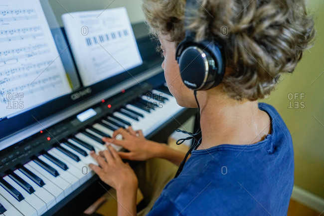 Boy playing a piano wearing headphones