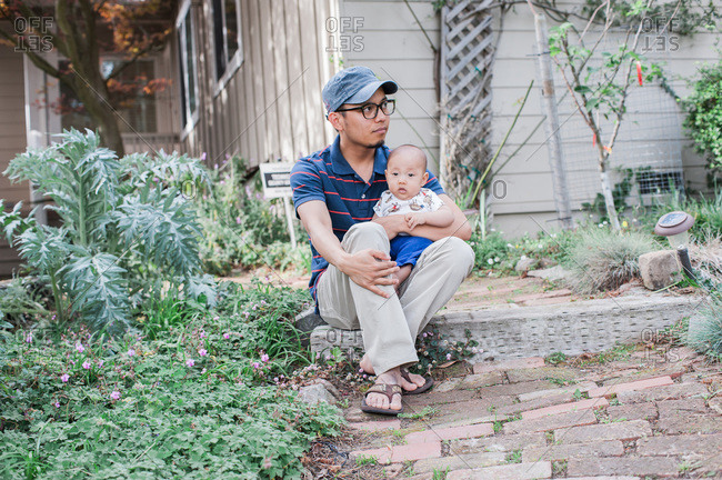 Father with son on lap while sitting on step in yard