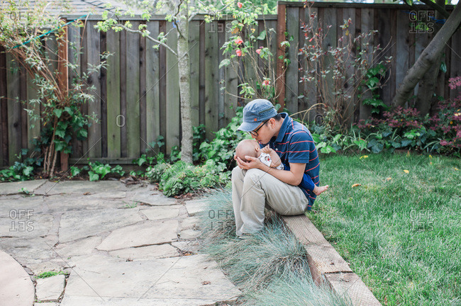 Father kissing son in the backyard