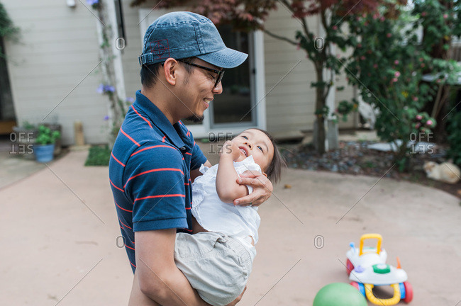Father carrying toddler in the backyard