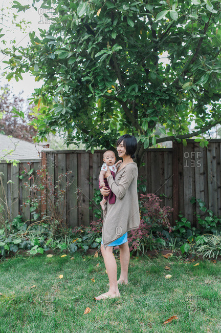 Mother standing in yard holding son