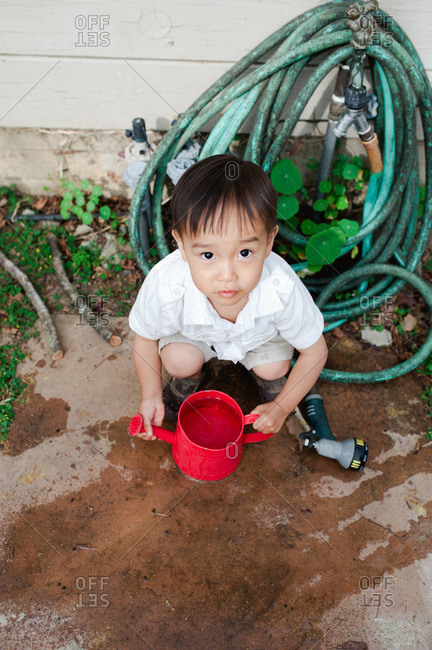 Boy with watering can filled with water equating next to garden hose