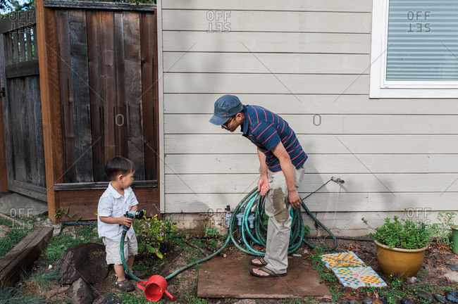Child hold garden hose with father with wet pants