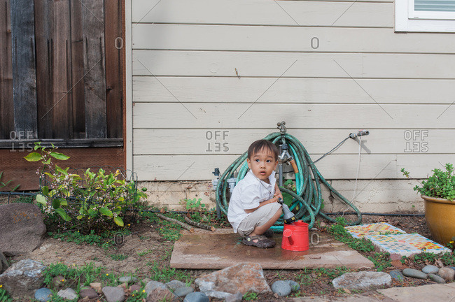 Young boy filling watering can with garden hose