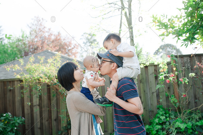 Mother holding baby boy while father kisses him with toddler on shoulders