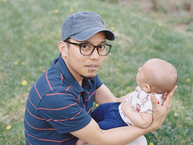 Young father sitting on ground holding baby