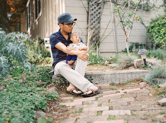 Young father in glasses and baseball hat sitting on step with his son
