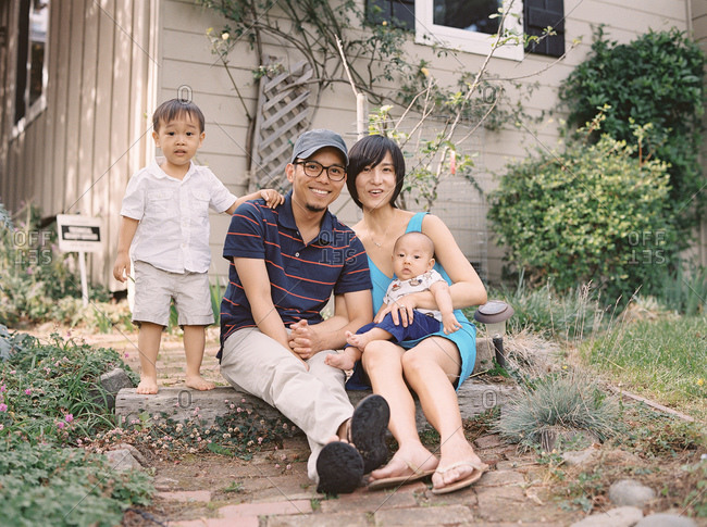 Young Asian family posing in front of house