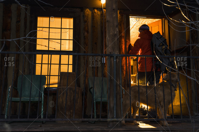Man and dog on cabin porch