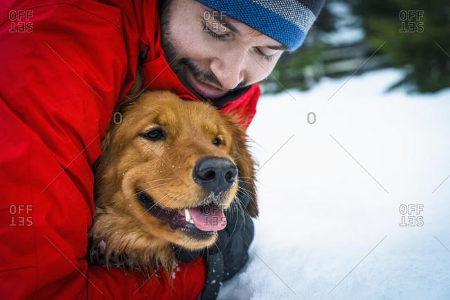 Man hugging dog in winter