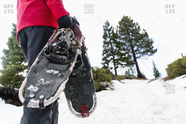 Man carrying pair of snowshoes