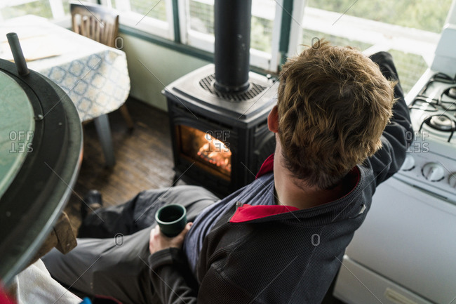Man warming up by cabin stove