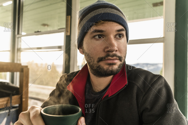 Man with steaming mug in cabin