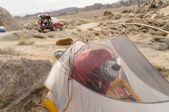 Man in tent in rocky campsite