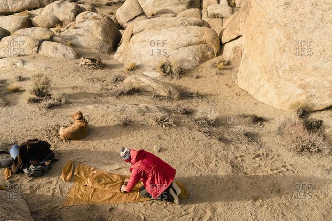 Man folding tent in rocky wilderness