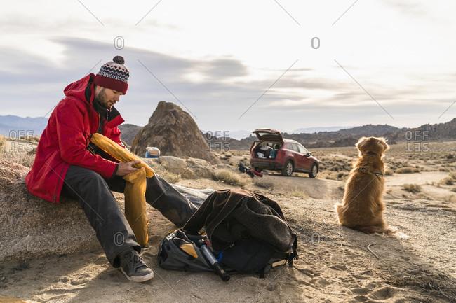 Man with tent bag near dog