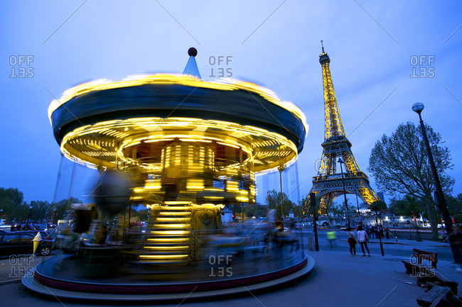 April 16, 2015: Carousel below the Eiffel Tower at twilight, Paris France