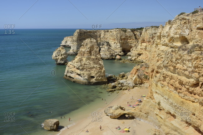 Overview of tourists on beach, sandstone cliffs and sea stacks at Praia da Marinha, Portugal