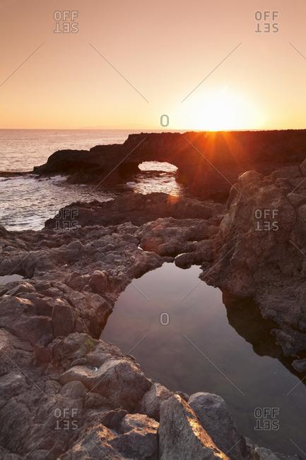 Rock arch at sunrise, Charco Manso Bay, Punta Norte near Echedo, UNESCO biosphere reserve, El Hierro, Canary Islands, Spain