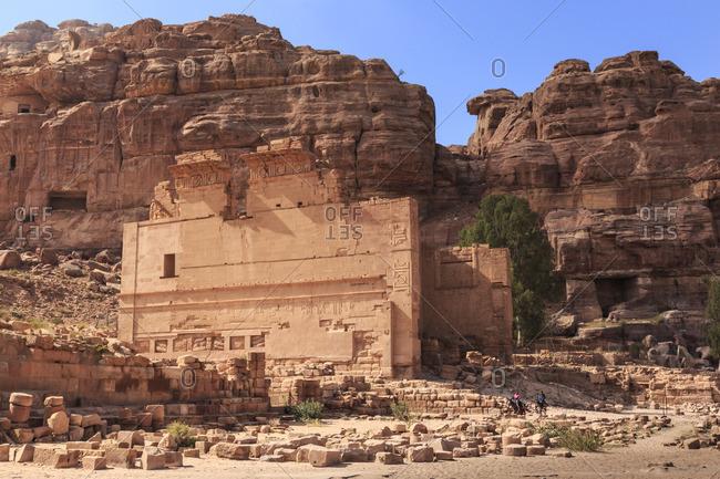 Local men on donkeys pass Qasr al-Bint temple, City of Petra ruins, Petra, Jordan, Middle East