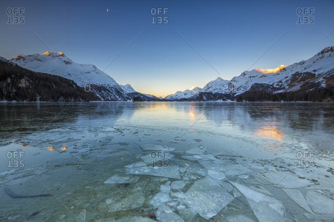 Sheets of ice on the surface of Lake Sils in a cold winter morning at dawn Engadine Canton of Graubunden Switzerland Europe