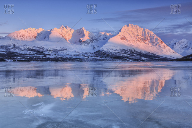 Snowy peaks are reflected in the frozen Lake Jaegervatnet at sunset Stortind Lyngen Alps Tromso Lapland Norway Europe