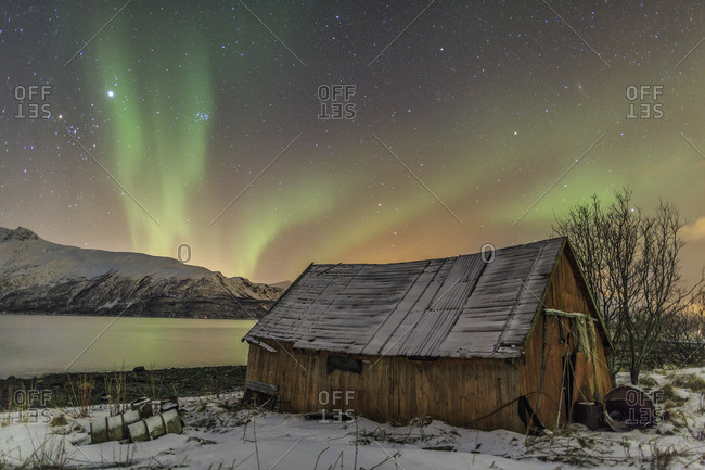 The Northern Lights illuminates the wooden cabin Svensby Lyngen Alps Tromso Lapland Norway Europe