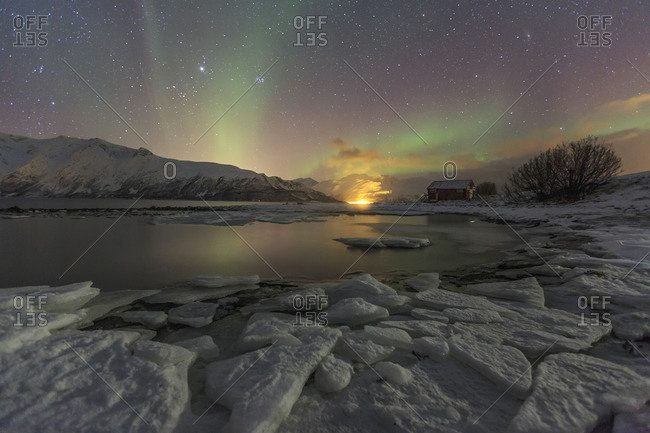 The Northern Lights illuminates the icy landscape in Svensby Lyngen Alps Tromso Lapland Norway Europe
