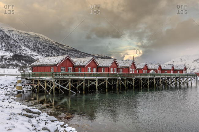 Typical red wooden huts of fishermen in the snowy and icy landscape of Lyngen Alps Tromso Lapland Norway Europe