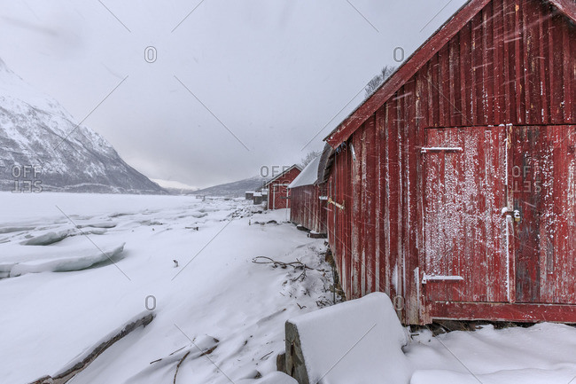 Typical wooden huts in the snowy landscape of Lyngseidet Lyngen Alps Tromso Lapland Norway Europe