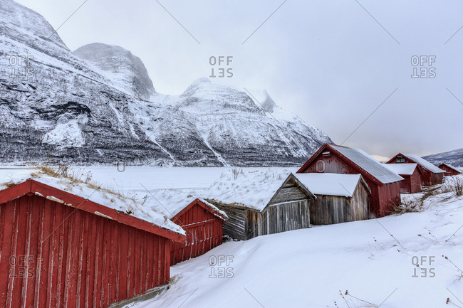 Typical wooden huts in the snowy landscape of Lyngseidet Lyngen Alps Tromso Lapland Norway Europe