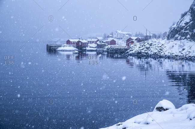 Heavy snowfall on the fishing village and the icy sea Nusfjord Lofoten Islands Norway Europe