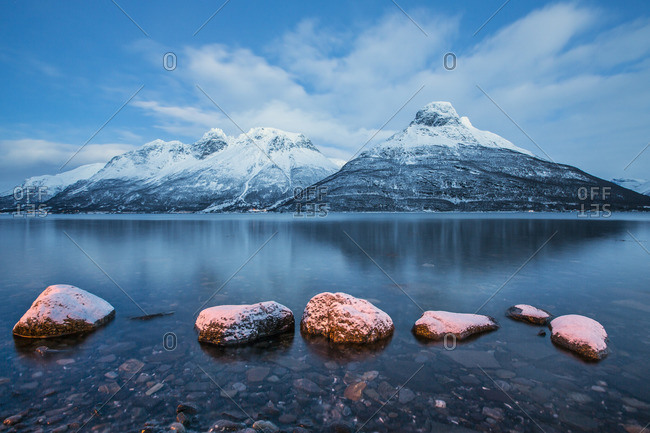 Blue sky at dusk and snowy peaks are reflected in the frozen sea Storfjorden Lapland Lyngen Alps Tromso Norway Europe