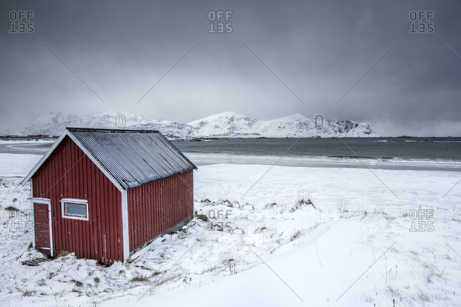 A typical house of the fishermen called rorbu on the snowy beach frames the icy sea at Ramberg Lofoten Islands Norway Europe