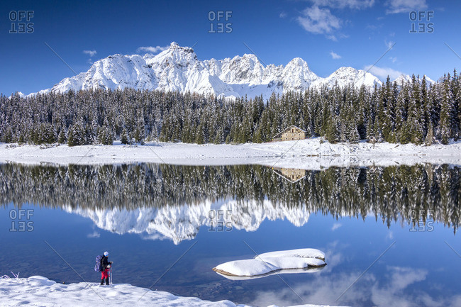 Hiker admires the snowy peaks and woods reflected in Lake Pali Malenco Valley Valtellina Lombardy Italy Europe