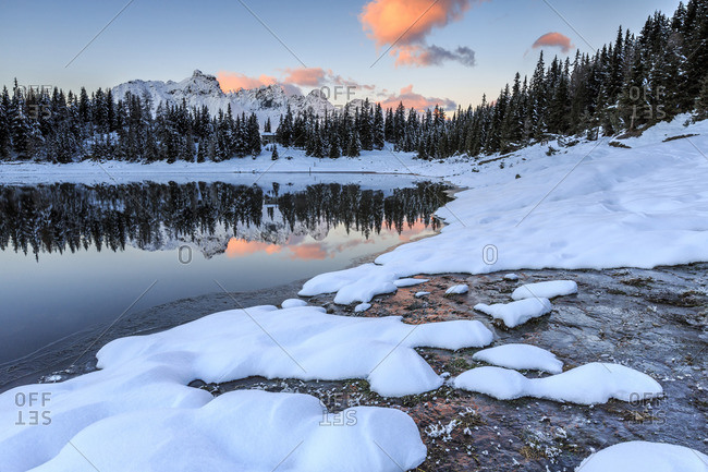 Woods and snowy peaks are reflected in Lake Pal�_ at sunrise Malenco Valley Valtellina Lombardy Italy Europe