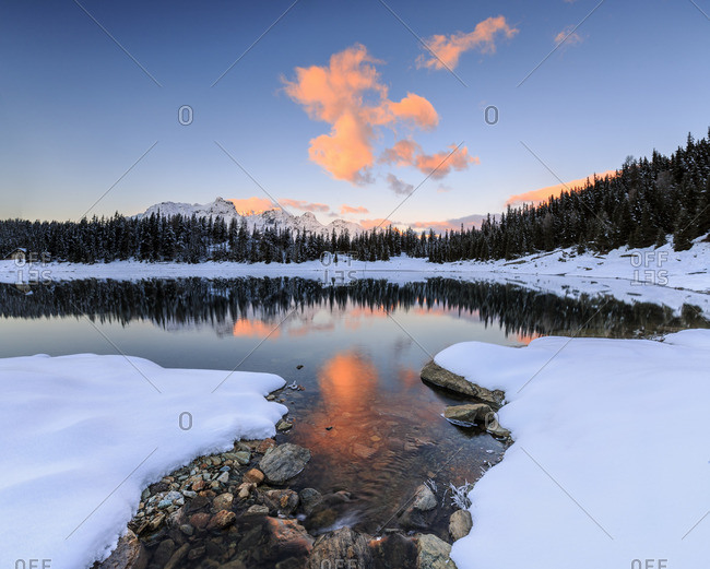 The colors of dawn on the snowy peaks and woods reflected in Lake Pali Malenco Valley Valtellina Lombardy Italy Europe