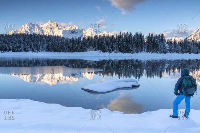 Hiker admires the snowy peaks and woods reflected in Lake Pal�_ at dawn Malenco Valley Valtellina Lombardy Italy Europe