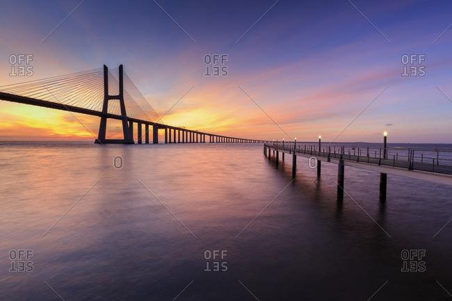 The colors of dawn on Vasco da Gama Bridge that spans the Tagus River in Parque das Na?_?�es Lisbon Portugal Europe