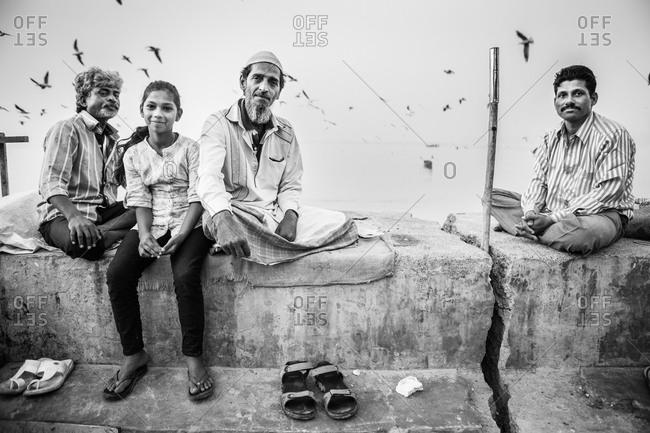 Mumbai, India - January 3, 2015: Men and girl sitting on a rooftop in Mumbai