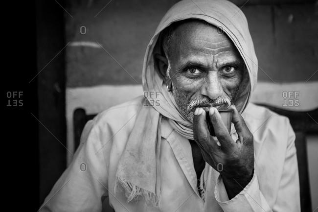 Karnataka, India - January 6, 2015: Portrait of an Indian man drinking tea