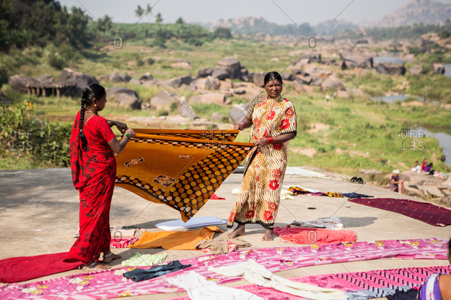 Karnataka, India - January 9, 2015: Women laying laundry out to dry on a large rock in India