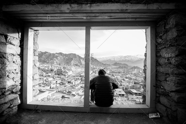 Man overlooking a city from the window of a Buddhist monastery in Ladakh, India