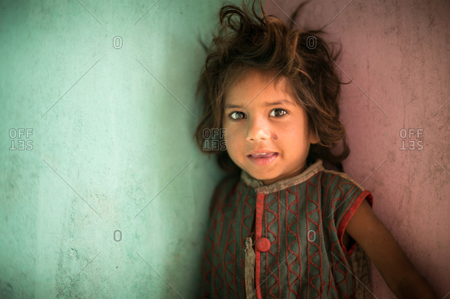 Jaipur, India - February 28, 2015: Portrait of a little girl beside multi-colored walls in Jaipur, India